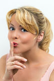 Woman gesturing for quiet. Young woman with finger to lips gesturing for quiet or silence, white background Stock Image