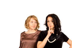 Woman gesturing for silence. Beautiful young women gesturing for silence with her finger raised to her lips watched by a friend with an amused expression Royalty Free Stock Photos