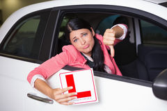 Woman gesturing thumbs down holding a learner driver sign Royalty Free Stock Photography