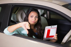 Woman gesturing thumbs down holding a learner driver sign. At new car showroom royalty free stock photo