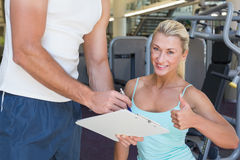 Woman gesturing thumbs up besides trainer with clipboard at gym Royalty Free Stock Images