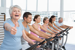 Woman gesturing thumbs up with class at spinning class Royalty Free Stock Images