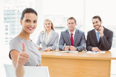 Woman gesturing thumbs up in front of corporate personnel officers. In office royalty free stock photography