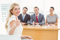 Woman gesturing thumbs up in front of corporate personnel officers. In office stock photos
