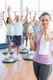Woman gesturing thumbs up with people stretching hands fitness studio Stock Image