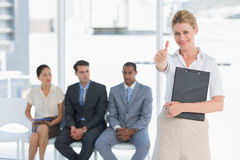 Woman gesturing thumbs up with people waiting for interview in office Stock Image