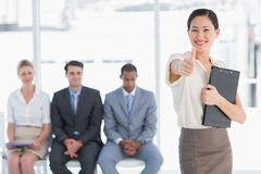 Woman gesturing thumbs up with people waiting for interview Royalty Free Stock Image