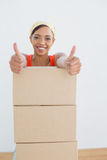 Woman gesturing thumbs up with stack of boxes in a new house Royalty Free Stock Images
