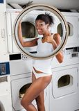 Woman Gesturing Thumbs Up While Standing By Dryer. Portrait of young woman in undergarments gesturing thumbs up while standing by dryer in laundry Royalty Free Stock Photos
