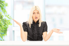 Woman gesturing uncertainty seated at home Stock Photos
