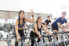Woman Gesturing Victory While Exercising On Spinning Bike In Gym. Excited sporty women gesturing victory sign while exercising on spinning bike by friends in gym Royalty Free Stock Images