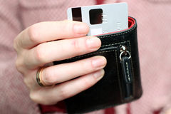 Woman get  out a credit card from purse in the shop Royalty Free Stock Photo
