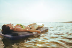 Woman get tan while lying on Inflatable mattress. In the middle of the lake on sunset Stock Image