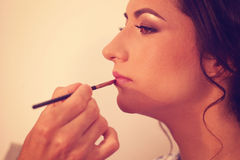 Woman geting lipstick on Royalty Free Stock Image