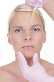 Woman gets beauty treatment. In her face Stock Photography