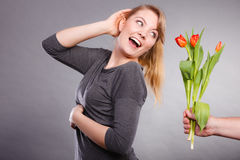 Woman gets bouquet of tulips from man. Royalty Free Stock Image