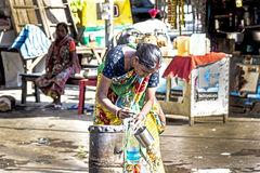 Woman gets clean water from a hydrant in the old part of Calcutt. CALCUTTA, INDIA - APR 7, 2013: woman gets clean water from a hydrant in the old part of Stock Image