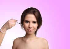 Woman gets cosmetic injection,  over pink background. Doctors hands making an injection. Beauty Treatment. Stock Image