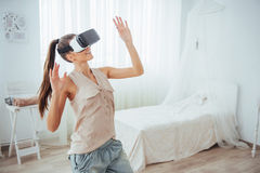 Woman gets experience of using VR-glasses virtual reality headset in a bright studio Royalty Free Stock Photography