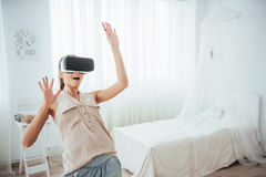 Woman gets experience of using VR-glasses virtual reality headset in a bright studio Royalty Free Stock Photo