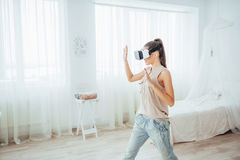 Woman gets experience of using VR-glasses virtual reality headset in a bright studio Royalty Free Stock Image