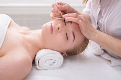 Woman gets eyelashes tinting by beautician at spa. Eyelashes tinting and coloring, spa beauty treatment and skincare. Woman getting procedure by beautician at Royalty Free Stock Photography