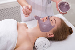 Woman gets face mask by beautician at spa. Face mask, spa beauty treatment, skincare. Woman getting facial nourishing mask by beautician at spa salon, side view Stock Photography