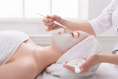 Woman gets face mask by beautician at spa. Face peeling mask, spa beauty treatment, skincare. Woman getting facial care by beautician at spa salon, side view Royalty Free Stock Image
