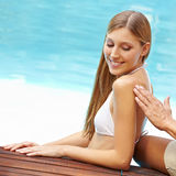 Woman gets her back lubed with sunscreen Stock Photography