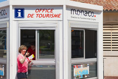 Woman gets maps and directions at the office of tourism booth in Monaco. Royalty Free Stock Photography