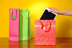 Woman gets out of the bags purchased tablet. Female gets out of the bags purchased tablet Stock Photo
