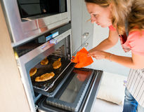 Woman gets out meat of the oven Royalty Free Stock Images