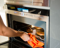 Woman gets out meat of the oven Royalty Free Stock Photo