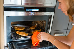Woman gets out meat of the oven Royalty Free Stock Photos
