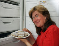 Woman gets out of refrigerator frozen meatba Stock Images