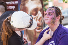 Woman Gets Realistic Zombie Makeup Before Atlanta Pub Crawl Event. Atlanta, GA, USA - July 25, 2015:  A makeup artist creates realistic fleshy wounds on a woman' Stock Photography
