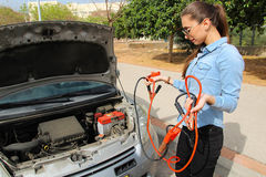 A woman with a broken car, hole cables waits for assistance Royalty Free Stock Photos