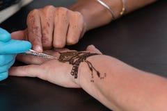 Woman Gets Temporary Henna Tattoo On Hand. Atlanta, GA, USA - September 12, 2015: An artist skillfully designs a henna temporary tattoo on a woman's hand at the royalty free stock images