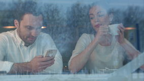 Woman getting bored in cafe while her boyfriend is busy with the phone stock video footage