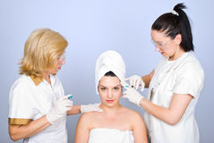 Woman getting botox inject to eyebrow. Woman getting botox injection to eyebrows from two plastic doctors,check also  Medical Stock Images