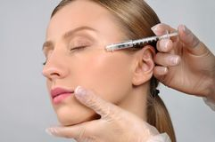Woman is getting botox injection. Anti-aging treatment and face stock photo