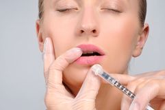 Beautiful girl receiving filler injection in lips. Botox. Cosmetic Treatment and Plastic Surgery. Woman is getting botox injection in lips. Cosmetic Treatment stock photo
