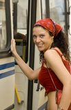 Woman getting on bus. Pretty woman in red getting on bus Royalty Free Stock Photography