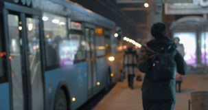 Woman getting on the bus arrived at the public transport stop. Woman at public transport stop in the evening. She taking away tablet computer as her bus arriving stock footage