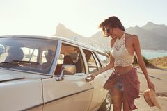 Woman Getting Into Car For Road Trip With Friends Stock Photo
