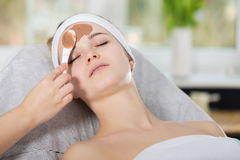 Woman getting chocolate mask treatment in spa. Beautician applying refreshing chocolate mask at young woman`s face Stock Photos