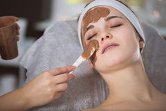 Woman getting chocolate mask treatment in spa. Beautician applying refreshing chocolate mask at young woman`s face Royalty Free Stock Photography
