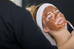 Woman getting chocolate mask treatment in spa. Beautician applying refreshing chocolate mask at young woman`s face Stock Images