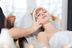 Woman getting chocolate mask treatment in spa. Beautician applying refreshing chocolate mask at young woman`s face Stock Photography