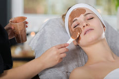 Woman getting chocolate mask treatment in spa. Beautician applying refreshing chocolate mask at young woman`s face Stock Image